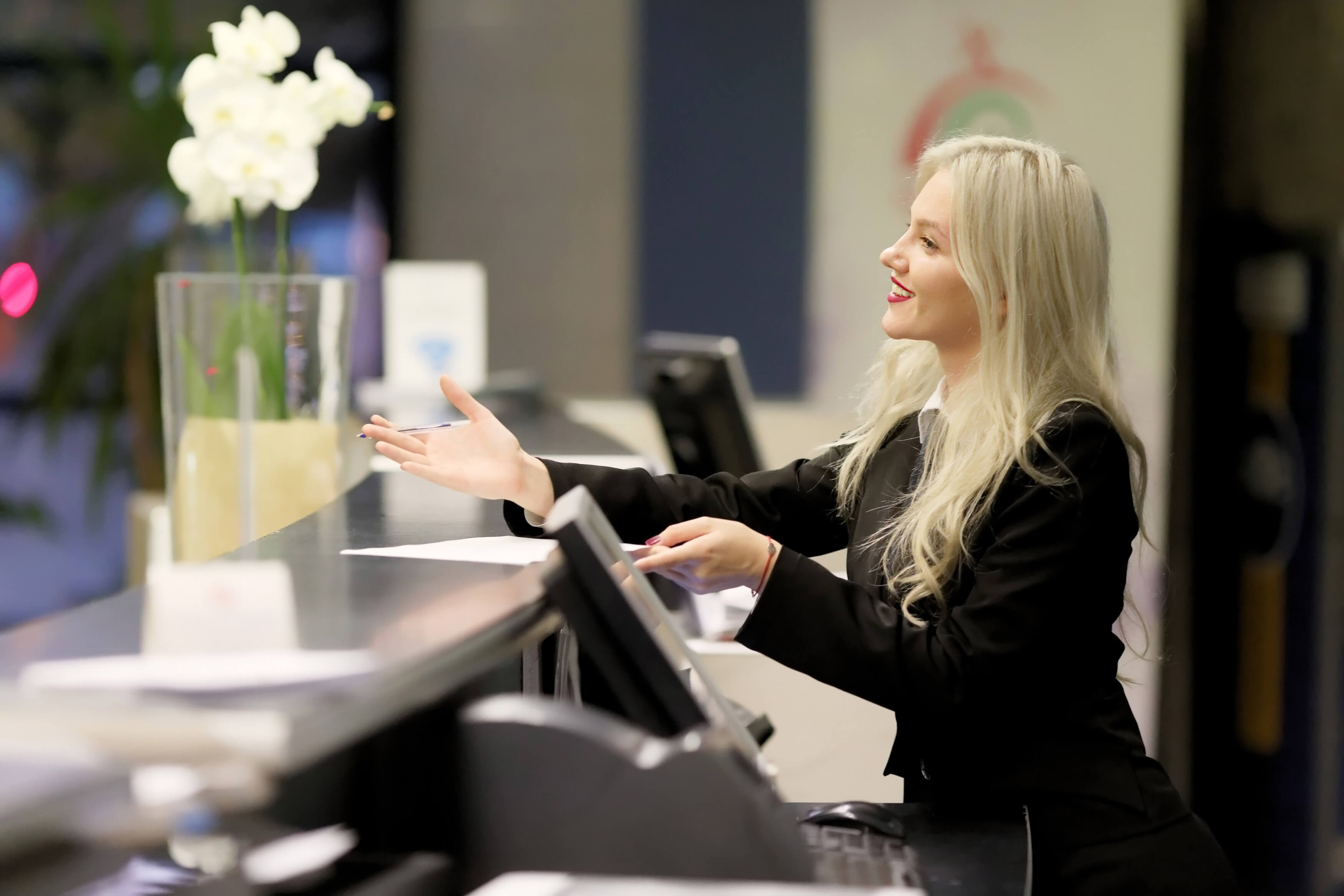 1st class protection blond girl concierge greeting from fron desk